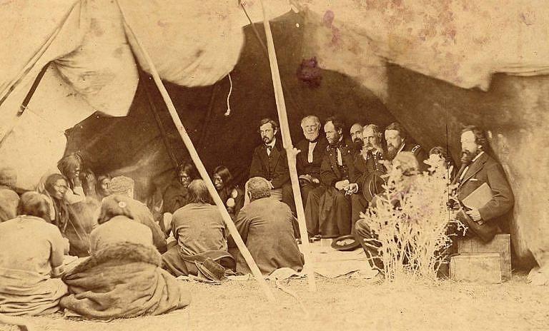 Jednání mezi indiánskými kmeny a zástupci vlády Spojených států. Na fotografii je v jednání smlouva z Fort Laeramie z roku 1868, která nahrazovala smlouvu z roku 1851.