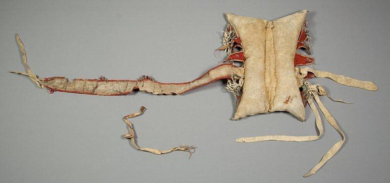 """Podbřišník černonožského polštářového sedla ze """"staré doby"""". Vyroben je z polovydělané kůže a na jedné straně je připevněn k sedlu na pevno, na druhé straně se přivazoval k oku ze jelenice nebo surové kůže."""