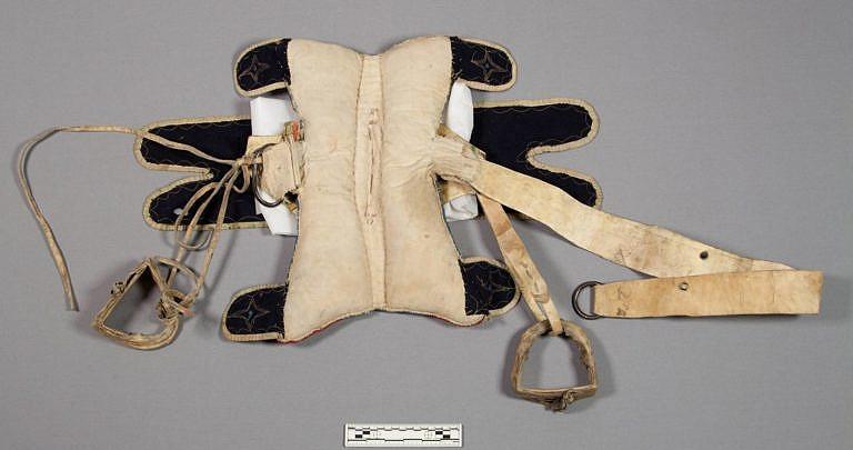 Podbřišník polštářového sedla novější konstrukce. Podbřišník je vyroben z polovydělané kůže a na jedné straně je připevněn k sedlu na pevno, na druhé straně se přivazoval k ocelovému oku. Ocelová oka prodávali indiánům bílí obchodníci. Šlo o stejná oka, která používali na svých sedlech běloši.