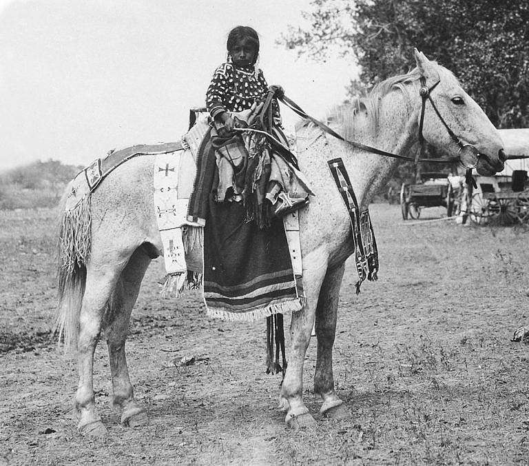 Holčička kmene Vran na svém koni, ozdobeném v transmontánním stylu. Její podsedlová deka je však lakotská, což ale není divné, protože lakotské podsedlové deky se šířily obchodem i k jiným kmenům, a to i nepřátelským.