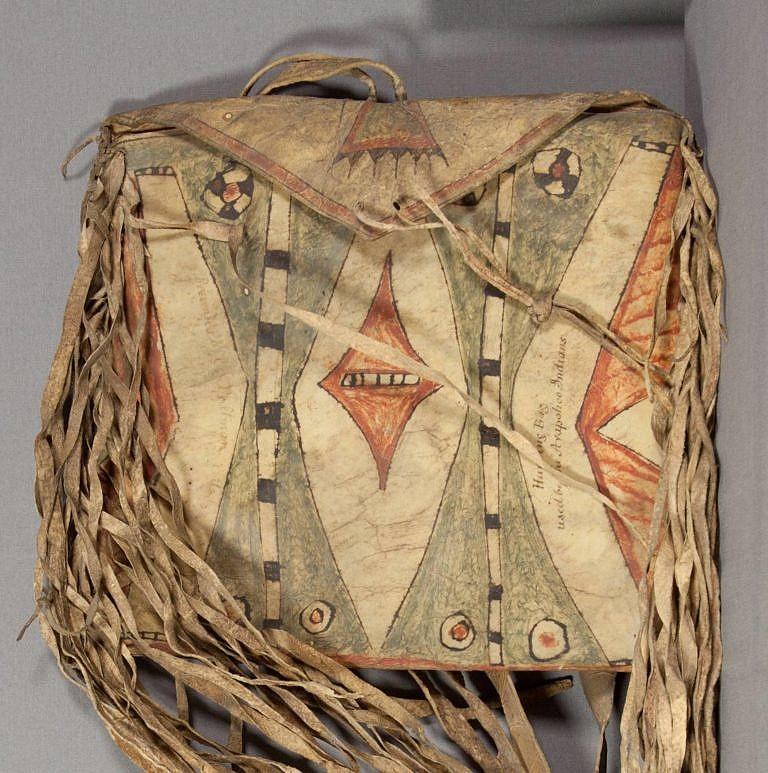 Plochá taška kmene Arapaho z 1. poloviny 19. století. Malována je červenou a zelenou barvou s černohnědou linkou. Tento exemplář je typickým příkladem staršího stylu malování surové kůže. Výrazné barvy přišly až mnohem později.