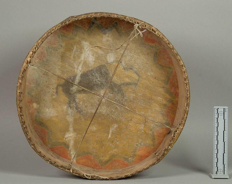 Bubínek vyrobený z dřevěného rámu a potažený surovou, nevydělanou kůži, nesoucí malbu z vnější strany. NMNH.
