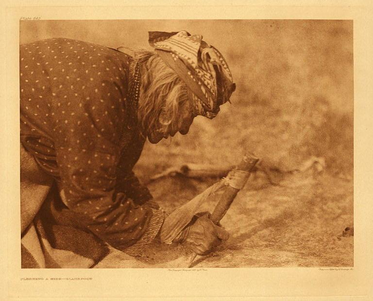 Indiánka na dobové fotografii mízdří kůži pomocí speciální škrabky, které se říká flesher (flešr). Foto E.Curtis.
