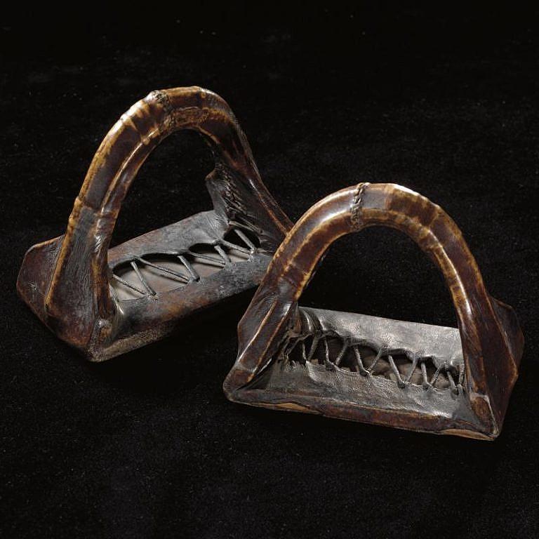 Indiánské třmeny. Vyrobeny jsou ze dřeva a zpěvněny potažením surovou kůží. Tato kůže nebyla změkčována, aby měla co nejvyšší pevnost. Chlupy byly odstraněny mírným zahnitím kůže nebo opatrně odškrábány skrejprem.