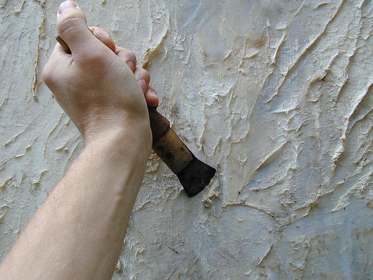Mízdření jelení kůže pomocí speciální škrabky, které se říká flesher (flešr). Autor článku.