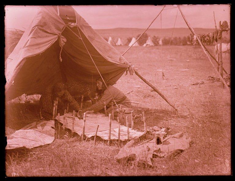 Ženy kmene Vran na dobové fotografii malují parfleše. Surová kůže je vypnutá na kolících a je stále vlhká. Ženy si postavily stínítko, aby kůže neschla tak rychle. Foto R.Throssel.