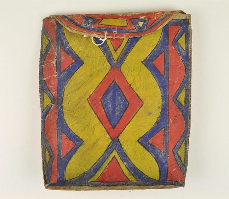 Plochá taška kmene Lakotů z 2. poloviny 19. století (rezervační období). Výrazné barvy a kombinace žluté, červené a modré jsou typické pro pozdější období, poslední čtvrtinu 19. století.