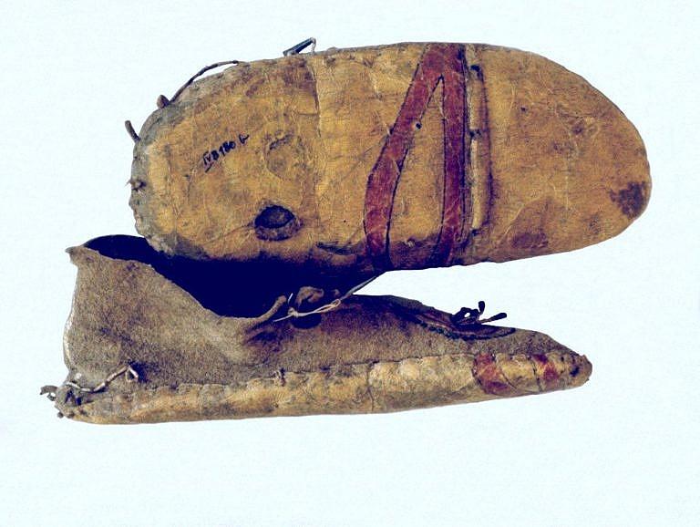 Mokasíny s bočním švem s dodatečnou podrážkou ze surové kůže. Evidentně bylo použito recyklace nějakého jiného, pomalovaného výrobku. Podrážka tak nese část malby původního výrobku.