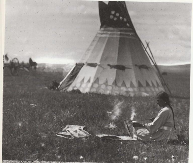 Indiánka kmene Černonožců kompletuje parfleše-obálky a právě propaluje dírky na provlečení kožených řemínků.