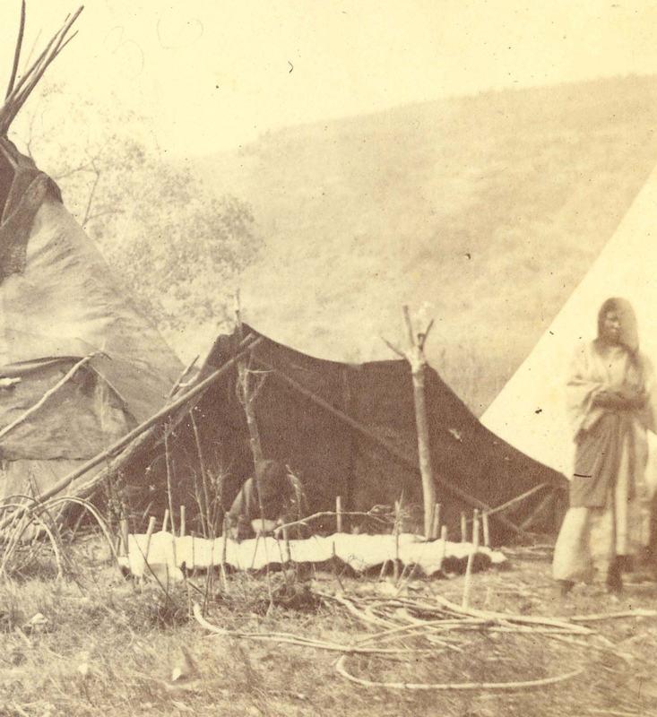 Indiánské ženy zpracovávající surovou kůži na vzácné dobové fotografii z předrezervačních dob. Aby nevysychala příliš rychle, postavily si indiánky stínítko proti slunci.