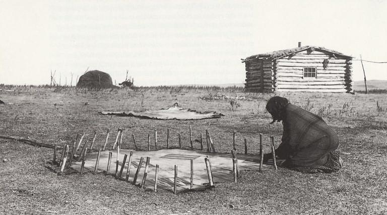 Indiánka kmene Lakotů při výrobě obálek-parfleší. Vzor si musela nejdříve rozmyslet a rozkreslit.