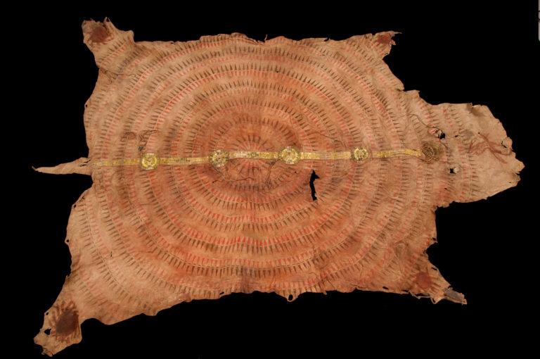 Bizoní plášť s vyšívaným pásem z ursoních ostnů. Je velice starý a pochází zřejmě až z 18. století. Kromě pásu je ozdoben malovaným symbolem sluneční péřové čelenky. Je uložen v Paříži v Muzeu člověka.