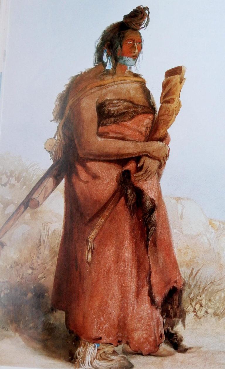 Náčelník kmene Atsinů s bizoním pláštěm. Plášť je obyčejný, není zdobený malbou ani výšivkou, pouze je nabarven červenou hlinkou. Ne všechny pláště byly zdobené, mnohé byly zcela prosté.