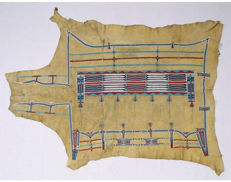 Bizoní plášť typu okraj o obdélník. Pravděpodobně lakotský. Ornamenty jsou místo malby vyvedeny výšivkou. Denver art museum.