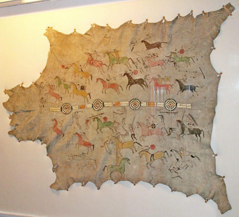 Nádherně zdobený plášť kmene Lakotů z 1. poloviny 19. století. Zdoben je ostnovým pásem a piktogramy. Ledermuseum Offenbach, Německo.