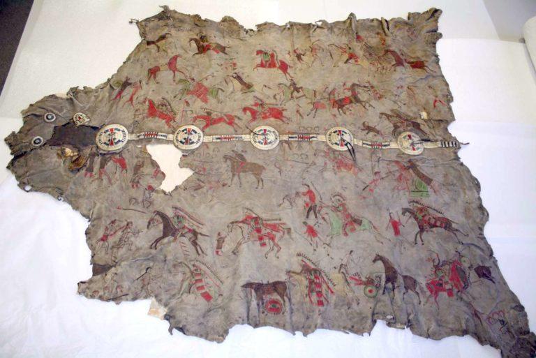 Bizoní plášť malovaný piktografickými výjevy válečných scén. Majitel pláště si na něj nechával namalovat své hrdinské skutky. Plášť je kromě kreseb zdoben i krásným pásem, vyšívaným ursoními ostny. Pennsylvania museum.