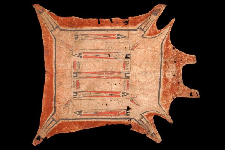 """Plášť z jelena nebo z bizona z oblasti Velkých jezer. Pochází patrně již ze 17. století a patří tak k nejstarším dochovaným indiánským plášťům na světě. Zřejmě se jedná o předchůdce vzoru """"okraj a obdélník"""". Muzeum člověka, Paříž."""