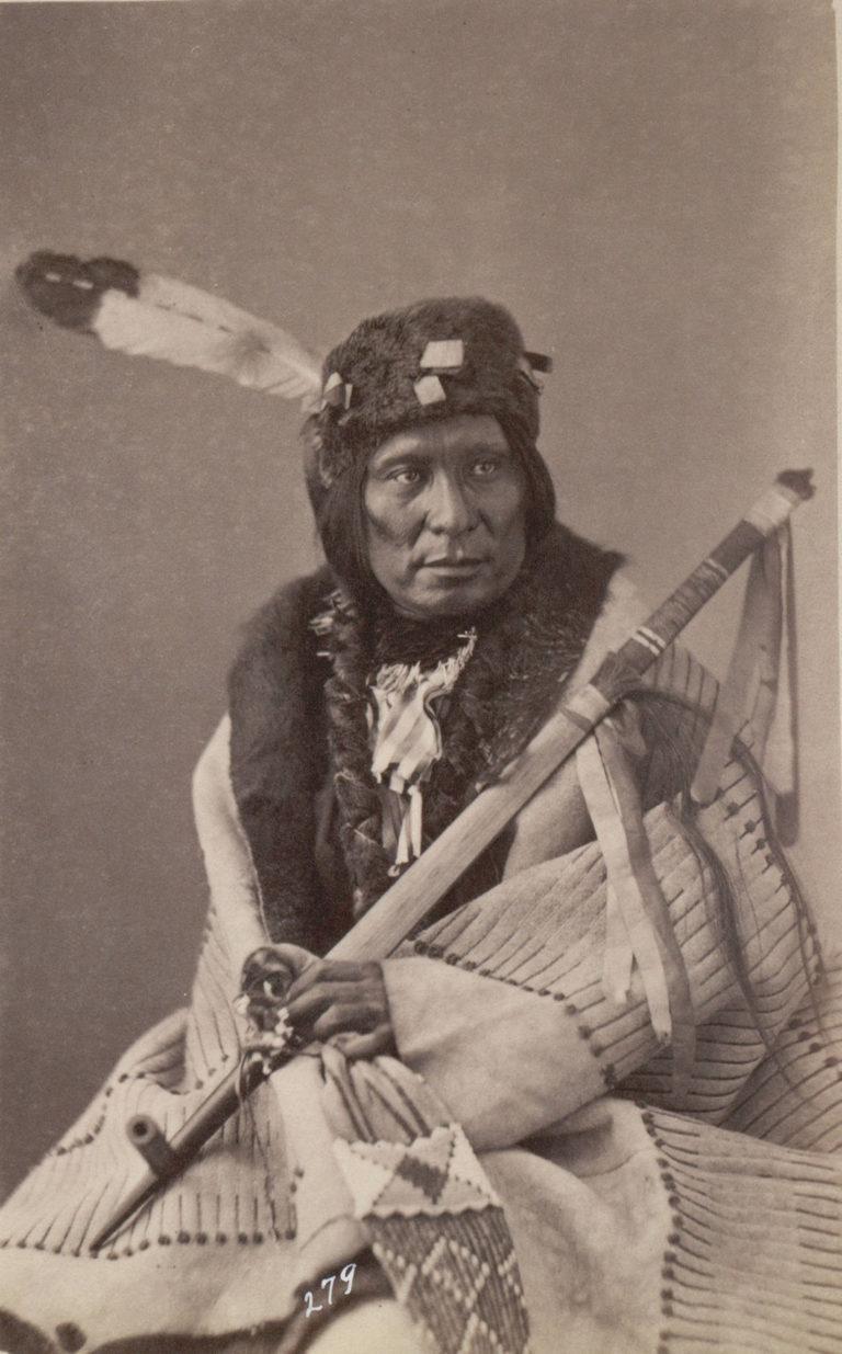 Šílený medvěd z kmene Lakotů na fotografii z roku 1872. Přes sebe má přehozený plášť s výšivkou bizoních proužků.