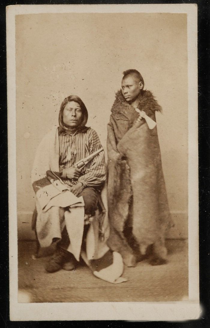 Dva Pónyové na dobové fotografii. Bojovník vpravo je zabalen do bizoního pláště zatímco jeho druh vlevo již má bělošskou Hudsons Bay deku.