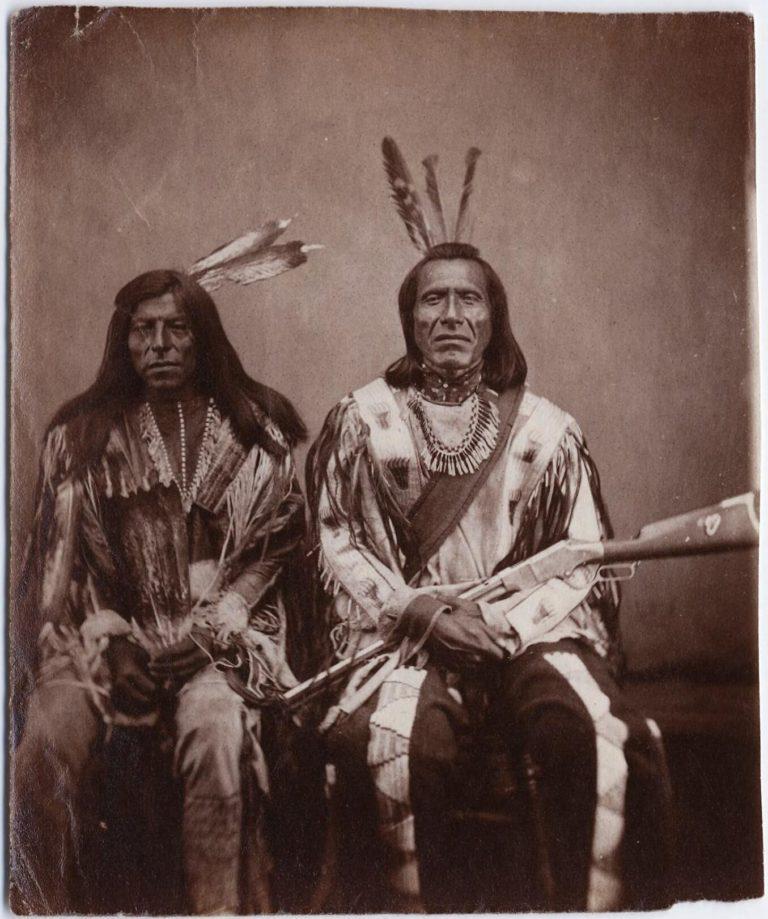 Šílený býk a Tetřívek, bojovníci kmene Atsinů na fotografii Stanley Morrowa z roku 1870. Bojovník vpravo má na kolenou opakovací pušku Henry.
