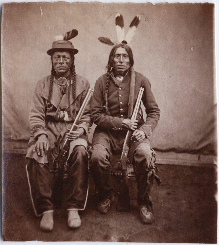 """Hledač síly a Štíhlý muž, bojovníci kmene Atsina. Oba jsou vyzbrojeni opakovacími karabinami """"yellow boy"""", Winchester 1866. Fotografie pochází z roku cca 1870. Autor Stanley Morrow."""