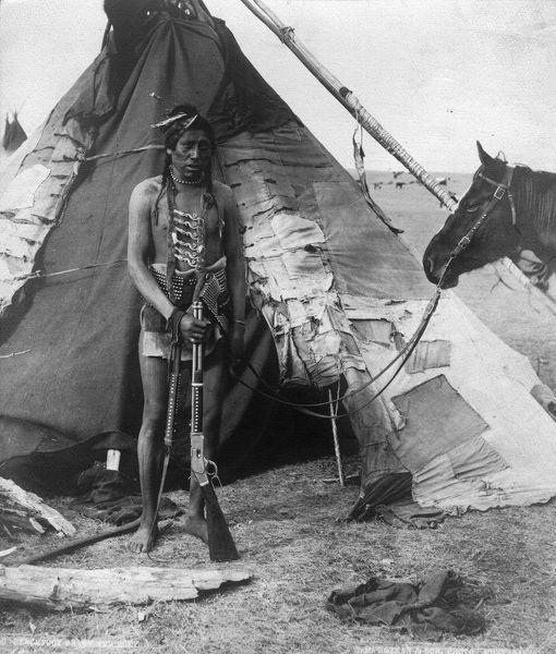 Bojovník kmene Černonožců s opakovací karabinou Winchester 1873 na dobové fotografii.