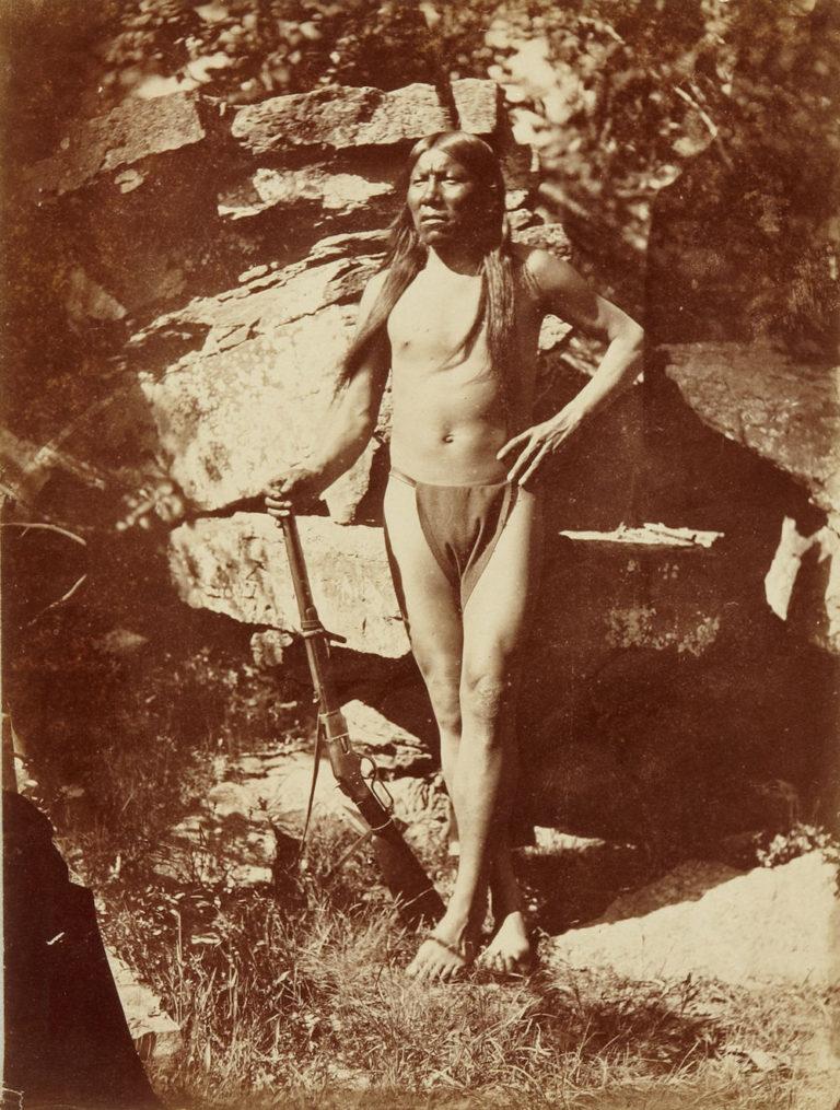 Malý medvěd z kmene Šajenů na dobové fotografii z roku 1875. Zbraní jeho volby je karabina Winchester 1866 yellowboy.