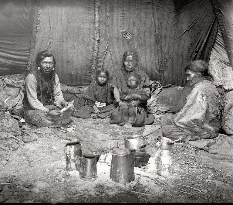 Interiér týpí indiánů z Kolumbijské plošiny. Fotografie pochází z rezervačního období. Bizoní kožešiny na zemi nahradily různé deky či jiné tkaniny. Všimněte si látkového liningu který probíhá za dřevěnými tyčemi.