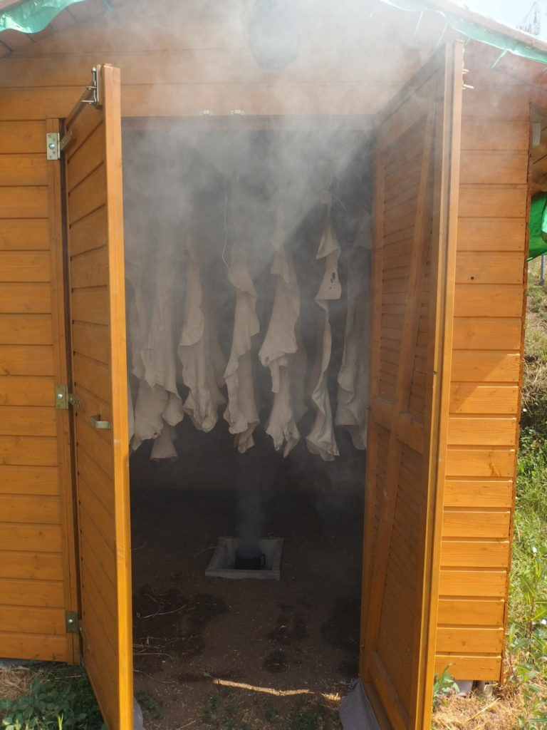 """Udírna na kůže, tzv. """"smokehouse"""". Rozmístění kůží je patrné. Zásadní je použití větráku, který je dobré umístit do kouřovodu nebo těsně nad něj. Pokud se neinstaluje větrák, kůže budou vyuzeny nerovnoměrně a uzení bude trvat déle."""