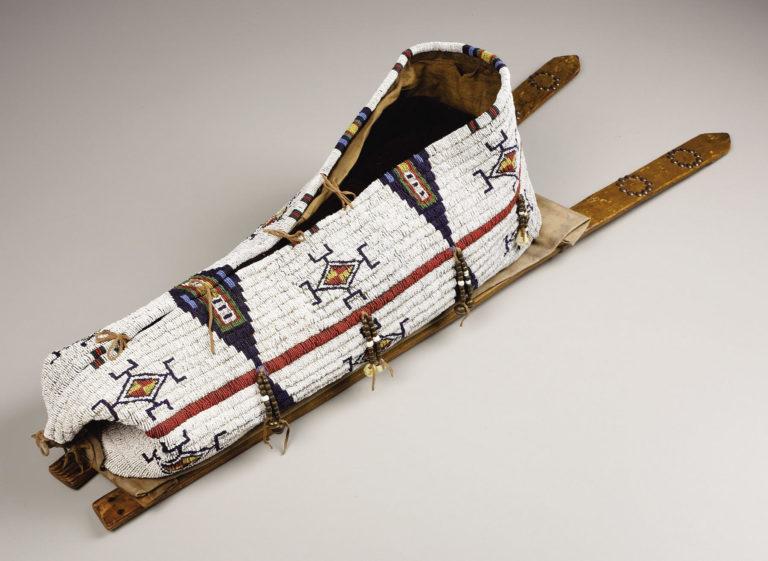 Dětská nosítka kmene Šajen. Lyžiny jsou zdobené vybíjením mosaznými cvočky.
