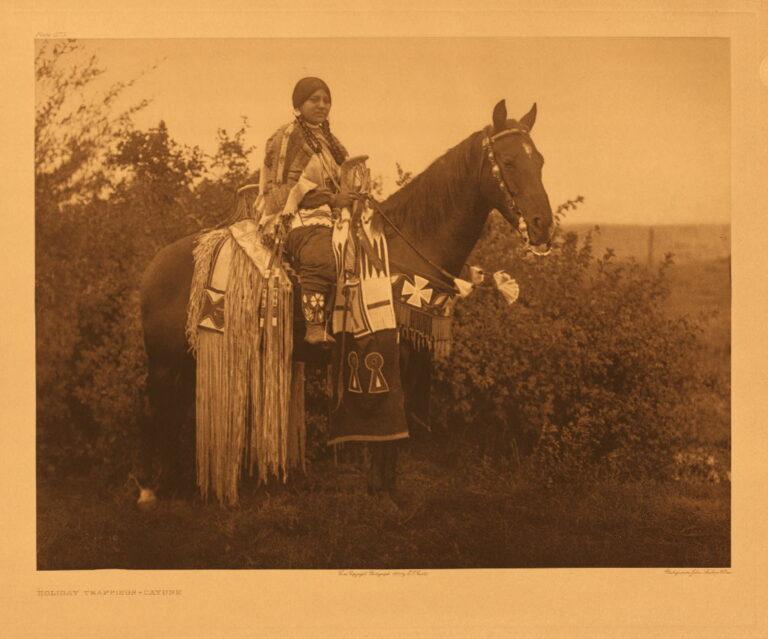 Indiánská žena z oblasti Plató na fotografii E.Curtise. Na zadní části sedla má zavěšený tubus s bohatým třásněním.