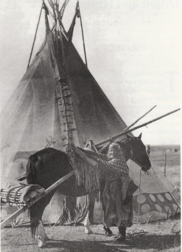 Žena kmene Černonožců na dobové fotografii. Všimněte si parfleše připevněné ke koňskému smyku.