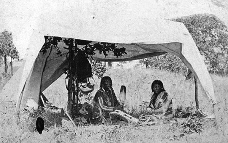 Indiáni pod provizorním stínítkem. Dobová fotografie.
