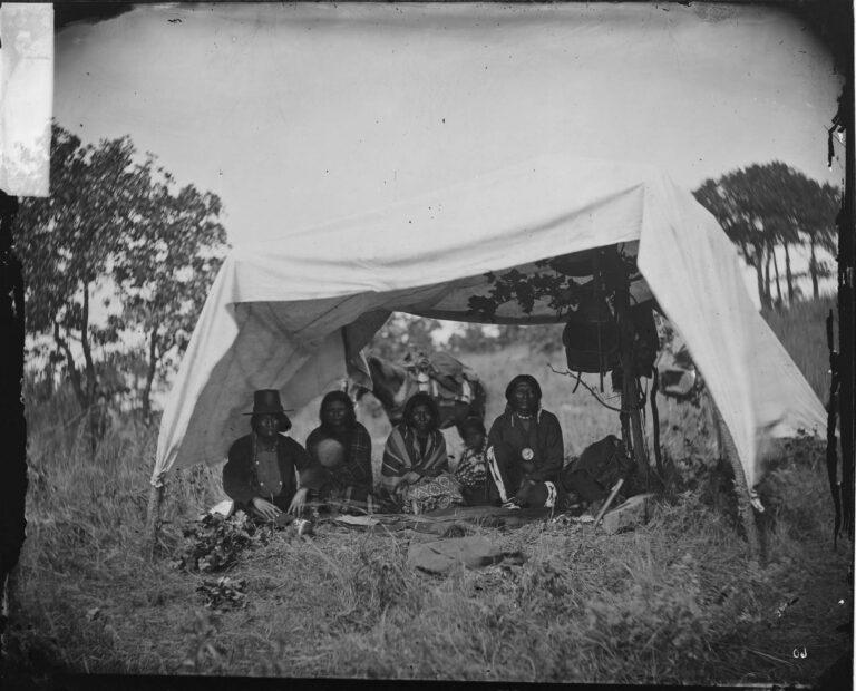 Skupina Šajenů na dobové fotografii z roku 1875. Jejich přístřešek je provizorně vyroben ze lněné nebo bavlněné plachty.