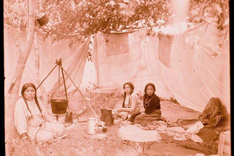 Indiánky kmene Vran vaří venku. Ze starého liningu si vyrobily provizorní zástěnu proti větru a slunci. Dobová fotografie R.Throssela.