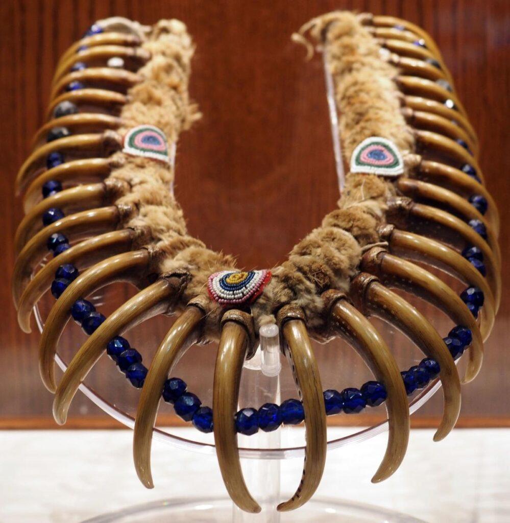 Náhrdelník kmene Meskwaki. Vyroben je z drápů prérijního grizzlyho a pochází z období kolem roku 1830.